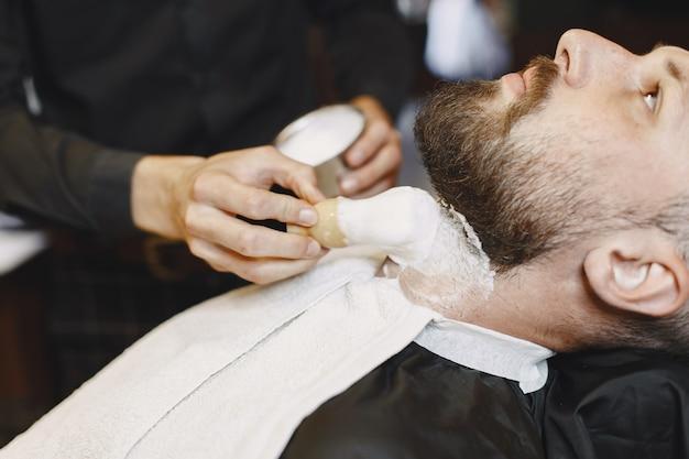 Мужчина с бородой. парикмахер с клиентом. человек с кистью. Бесплатные Фотографии