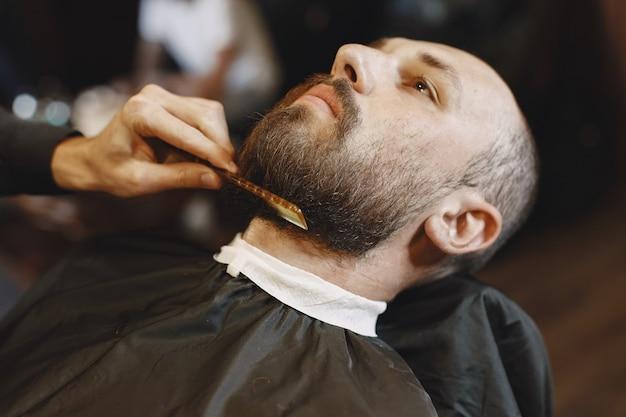 Мужчина с бородой. парикмахер с клиентом. человек с расческой и ножницами Бесплатные Фотографии