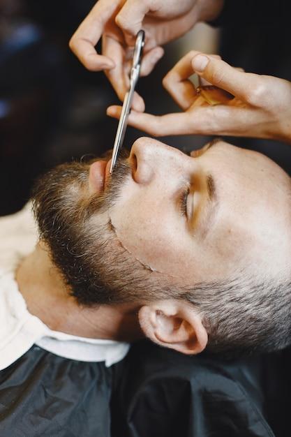 あごひげを生やした男。クライアントと美容師。くしとはさみを持つ男 無料写真