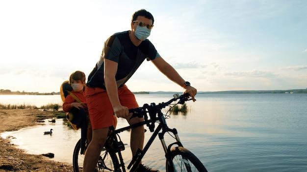 Мужчина с ребенком на велосипеде в защитных масках Premium Фотографии