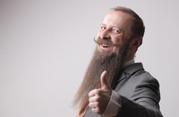 灰色の壁の前に親指を立てて立っている長いあごひげと口ひげを持つ男 無料写真