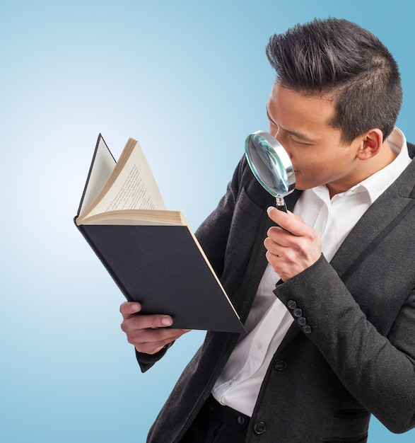 Man with a magnifying glass looking at a book Free Photo