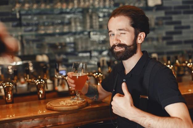 口ひげとあごひげを生やした男がバーに立ち、グラスからアルコールを飲みます。 無料写真