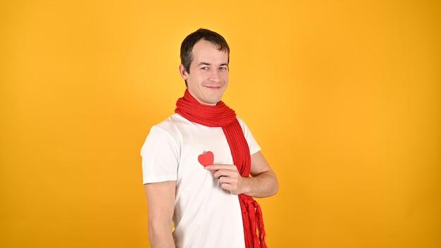 Человек с красным сердцем в руках на желтом Premium Фотографии
