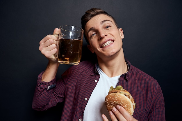 ジャンクフードのトレイを持つ男:ハンバーガーとフライドポテト、ビール Premium写真