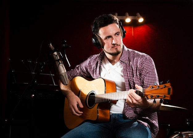 Man with acoustic guitar looking away Free Photo