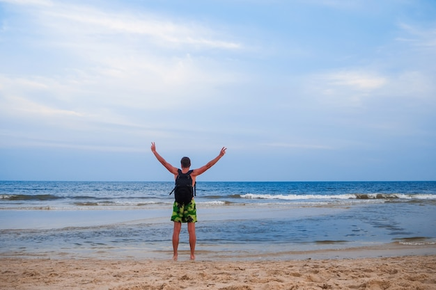 Man with a backpack on the background of the sea Premium Photo