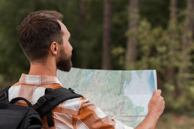 Человек с рюкзаком, глядя на карту во время кемпинга Бесплатные Фотографии