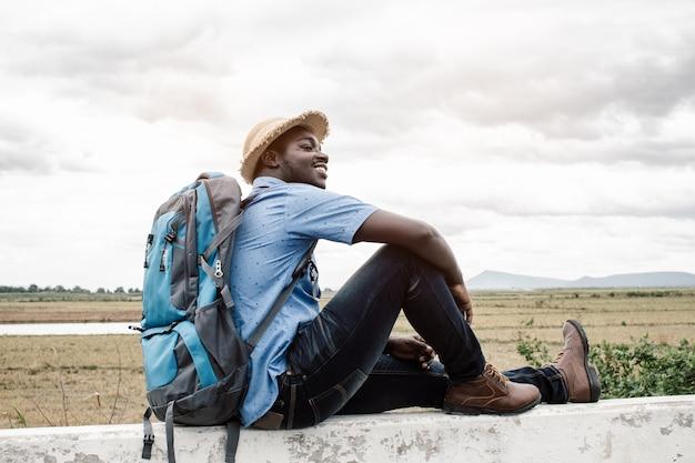 Человек с рюкзаком сидит на каменном заборе Premium Фотографии
