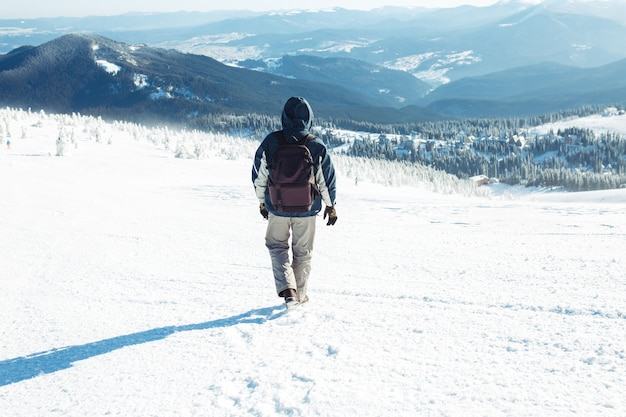 Man with backpack trekking in mountains. cold weather, snow on hills. winter hiking. winter is coming, first snowfall. concept of travel, rest, relaxation Premium Photo