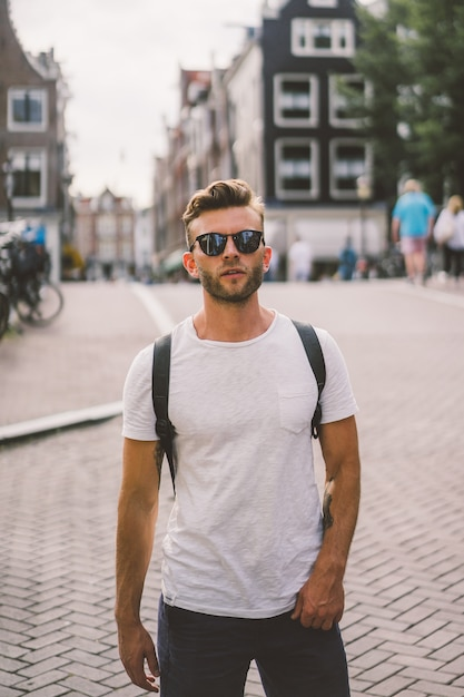 A man with a backpack walks through the streets of amsterdam. Free Photo