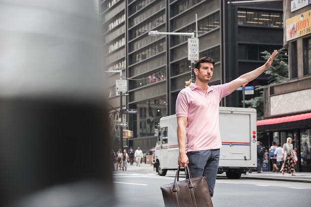 Man with bag hailing cab Free Photo