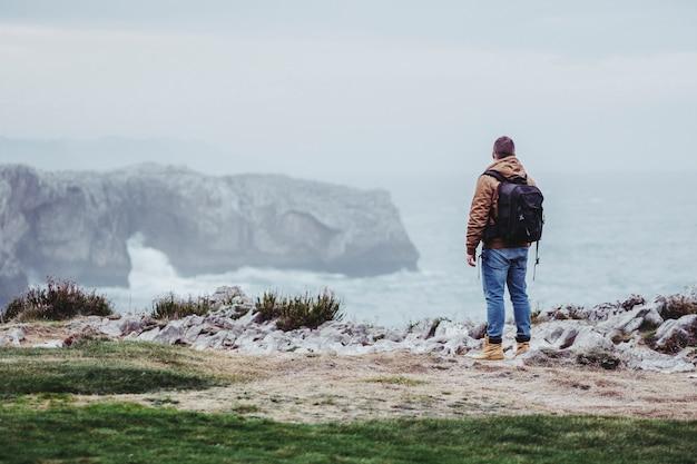 Man with bag tourist on cliffs Premium Photo