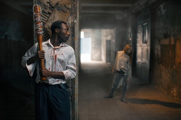 野球のバットを持った男がゾンビを殺す準備をし、廃工場で致命的な追跡をします。街の恐怖、不気味な這いつくばりの攻撃、終末の黙示録、血まみれの怪物 Premium写真