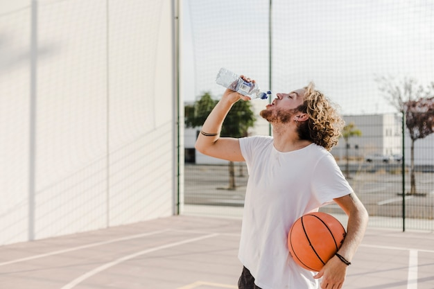 Man with basketball drinking water Free Photo