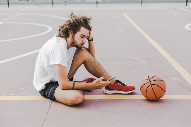 Man with basketball sitting in court using cellphone Free Photo
