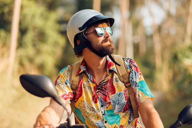 Man with beard in colorful tropical shirt sitting on motorbike Free Photo