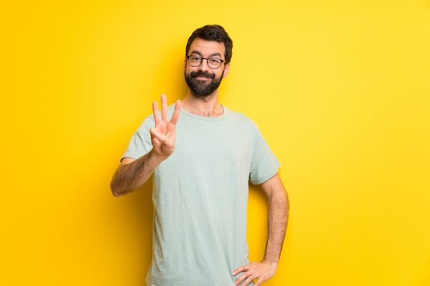 Man with beard and green shirt happy and counting three with fingers Premium Photo