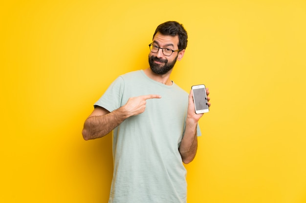 Man with beard and green shirt happy and pointing the mobile Premium Photo