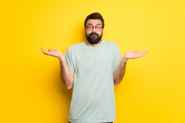 Man with beard and green shirt having doubts while raising hands and shoulders Premium Photo