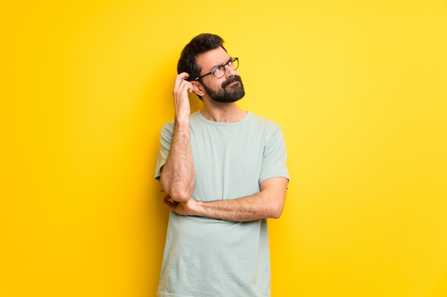 Man with beard and green shirt having doubts while scratching head Premium Photo