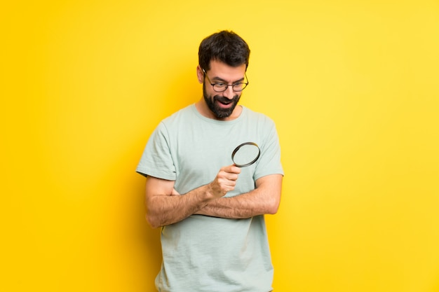 Man with beard and green shirt holding a magnifying glass Premium Photo