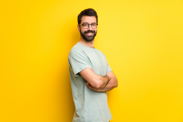 Man with beard and green shirt keeping the arms crossed in lateral position while smiling Premium Photo