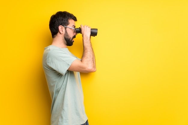Man with beard and green shirt and looking in the distance with binoculars Premium Photo