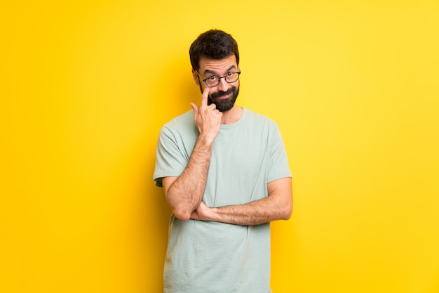 Man with beard and green shirt looking to the front Premium Photo