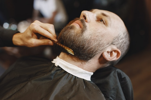 Uomo con la barba. parrucchiere con un cliente. uomo con un pettine e delle forbici Foto Gratuite
