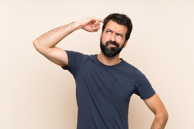 Man with beard having doubts and with confuse face expression Premium Photo