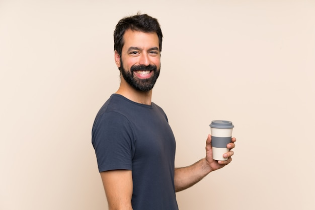 Man with beard holding a coffee with surprise facial expression Premium Photo