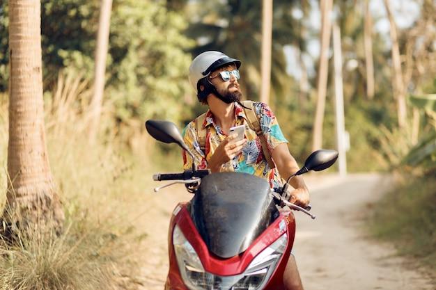 バイクの上に座ってカラフルなトロピカルシャツのひげを持つ男 無料写真