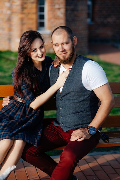 A man with a beard sits on a bench with a beautiful woman Premium Photo