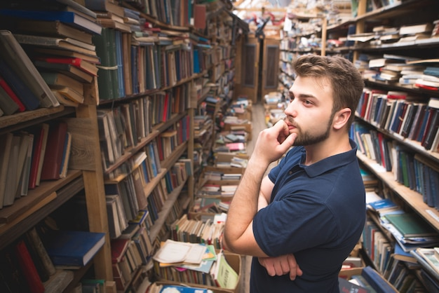 Premium Photo | Man with a beard standing on a public library and looking  at the bookshelf