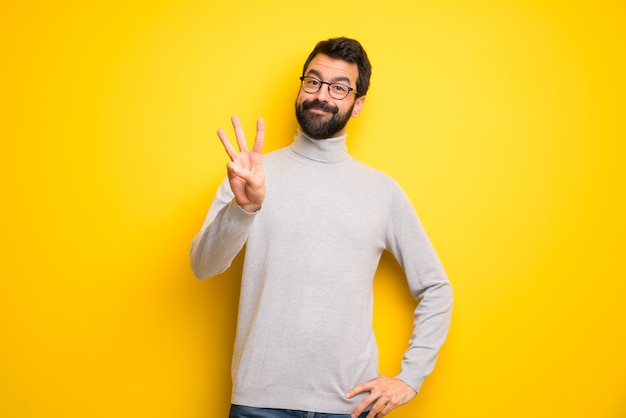 Man with beard and turtleneck happy and counting three with fingers Premium Photo