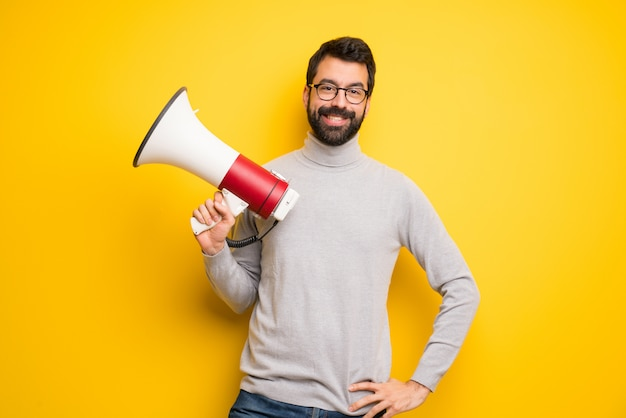 Man with beard and turtleneck holding a megaphone Premium Photo