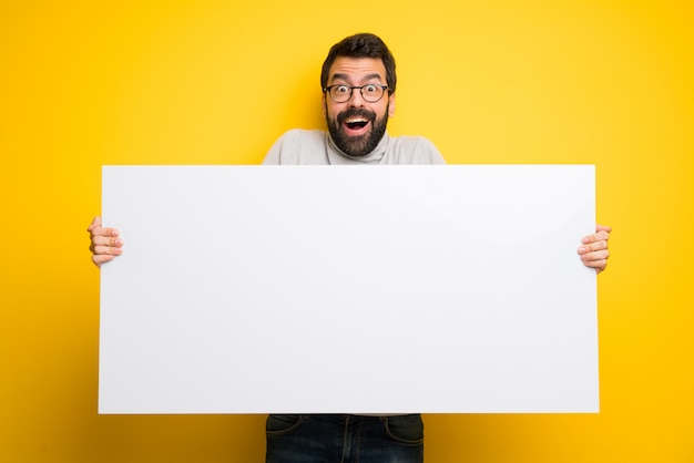 Man with beard and turtleneck holding a placard for insert a concept Premium Photo