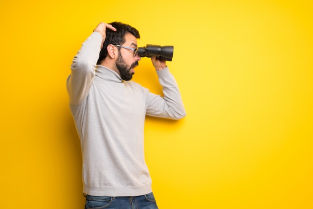 Man with beard and turtleneck and looking in the distance with binoculars Premium Photo