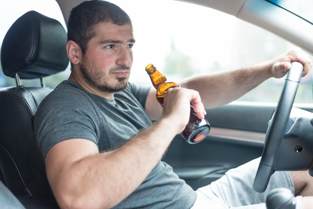 Man with beer driving car Free Photo