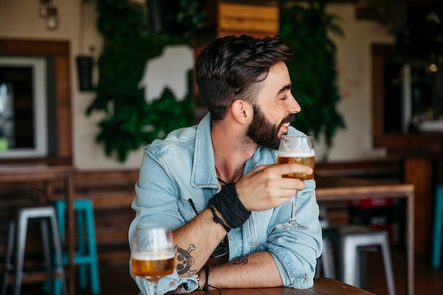 Man with beer looking to his left Free Photo