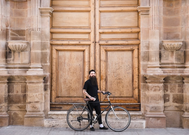 Man with bicycle standing in front of closed large vintage wooden wall Free Photo