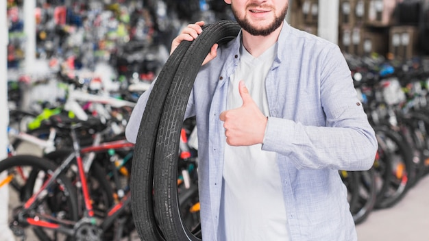 Man with bicycle tires gesturing thumb up Free Photo