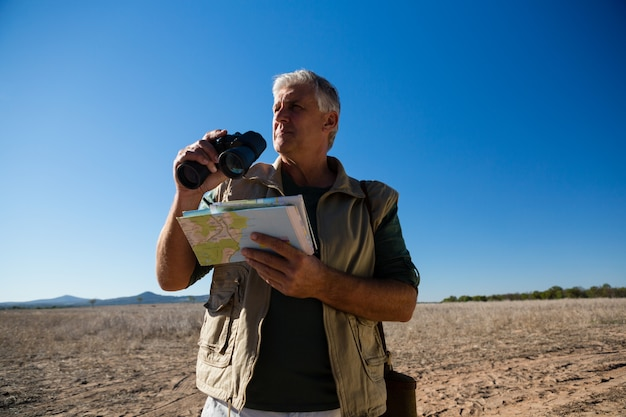 双眼鏡と地図上に立っている風景を持つ男 無料写真