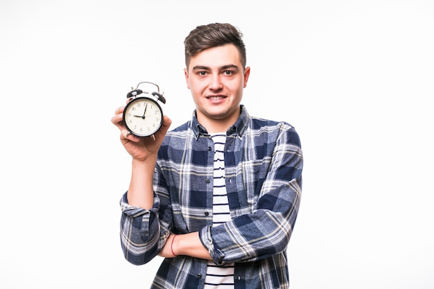 Man with black hair holds red alarm-clock dressed in casual clothes Free Photo