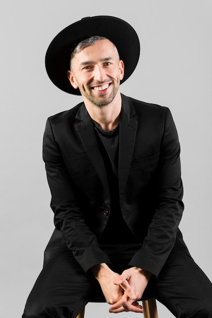 Man with black hat smiling and sitting on chair Free Photo