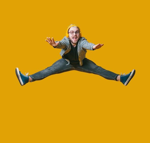 금발 머리와 수염을 가진 남자는 이어폰을 통해 음악을 들으면서 노란색 스튜디오 벽에 점프 프리미엄 사진