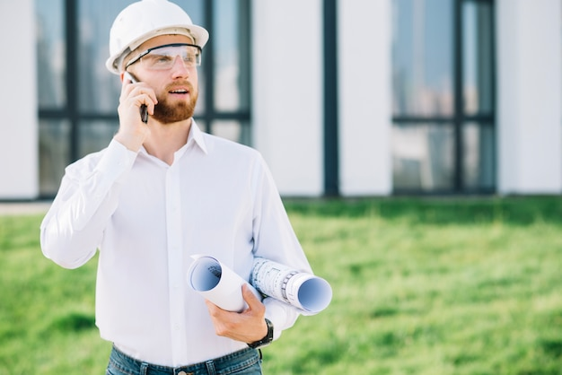 Man with blueprints talking on phone Free Photo