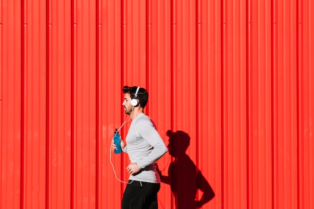 Man with bottle running near red wall Free Photo