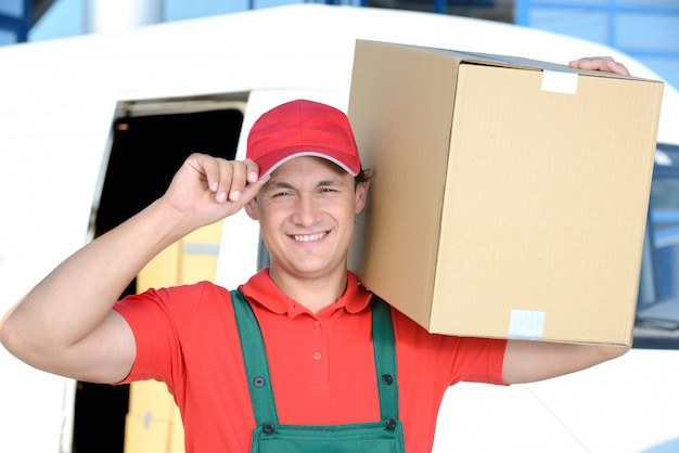 Man with a box on his shoulder carries a delivery for a man. Premium Photo